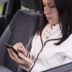 Woman Writes a Message On a Smartphone Sitting In The Car