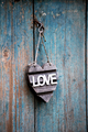 Hearted shaped Love sign hanging on an old door