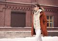 Fashion stylish man wearing a jacket and sunglasses walking in c