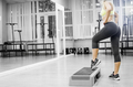 Sportive young woman doing exercise with barbell in the gym.