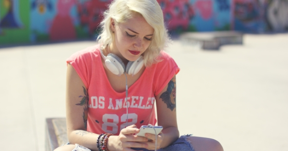 Download Young Woman Searching For Tunes On Her Mobile nulled download