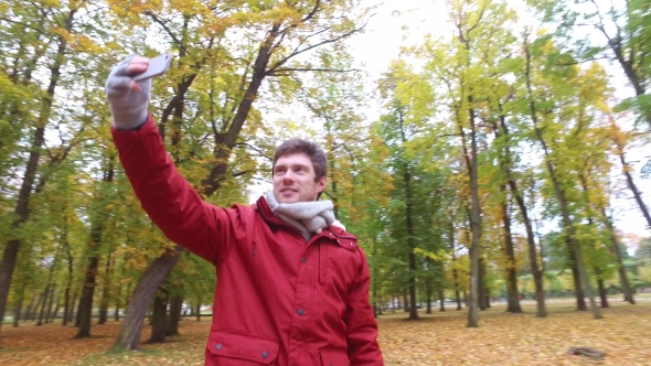 Download Man With Smartphone Taking Video At Autumn Park nulled download