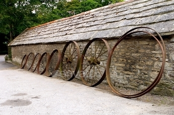 Row of old farm wheels leaning against a rustic old stone building