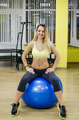 Cheerful pretty young fitness woman sitting on pink fitball and looking back over white background