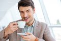 Happy smiling businessman in jacket drinking coffee indoors