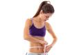 Sportive woman measuring her waist