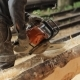 Man Cuts Off Beam Chainsaw For Future Home. Construction Works With a Wooden Structure.