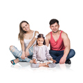 Happy young family sitting on the floor,