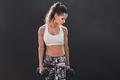 Female fitness model exercising with dumbbell