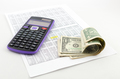 Calculator and money on the paper with financial data sheets