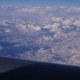 View Through An Airplane Window In The Blue Sky In Clouds
