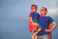 Father and son playing superhero outdoors at the day time.