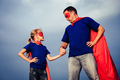 Father and daughter playing superhero outdoors at the day time.