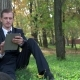 Businessman Sitting With a Tablet In The Park
