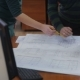 Team Of Engineers Working Together With Blueprint At a Desk.