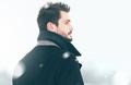 Portrait of fashion handsome elegant free man in winter snowstor