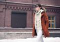 Fashion man wearing a jacket walking in city over brick wall bac