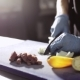 Hands Of Chef In Gloves Cutting An Onion In Commercial Kitchen