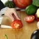 Woman Cuts Red Tomato Among The Fresh Vegetables