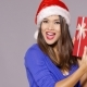 Excited Woman In a Santa Hat Holding  Gift