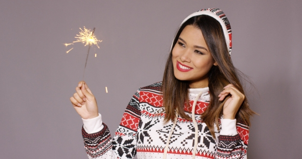 Young Woman Celebrating Christmas With a Sparkler