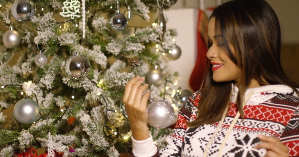 Attractive Woman Decorating a Christmas Tree