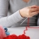 Woman Measuring Knitted Item And Making Notes