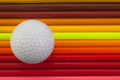 Detail of rainbow  colorful pencil and golf ball on the desk
