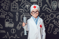 Happy little boy as a doctor in glasses holding syringe on dark background with pattern