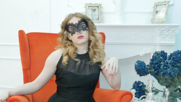 VideoHive Beautiful Young Woman In a Black Carnival Mask At a Party In a Red Armchair 18630081