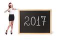 Business woman in xmas hat stands near chalkboard