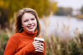 Woman holding to go coffee in autumn park