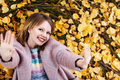 Young girl in pink coat lying on yellow leaves