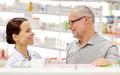 happy pharmacist talking to senior man at pharmacy