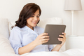 happy pregnant woman with tablet pc at home