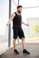 Concentrated fitness man doing cardio exercises with skipping rope outdoors