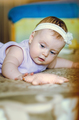 Portrait of a 7 month cute baby girl with a headband lying down on her stomach