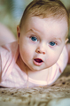 Portrait of a 7 month cute baby girl and lying down on her stomach