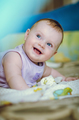 Portrait of a 7 month smiling cute baby girl and lying down on her stomach