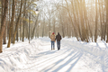 happy couple walking through a snowy forest in winter
