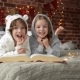 Cute Smiling Sister And Brother Reading a Book And Laughing At The Home In a Christmas Time. They