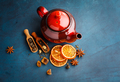 Teapot with dry tea over the blue background.