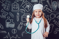 Little girl in doctor costume holding sthetoscope on dark background with pattern
