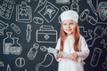 Little girl in doctor costume holding syringe on dark background with pattern