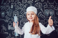 Little girl in doctor costume holding syringe and shows class on dark background with pattern