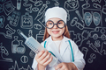 Happy little girl in doctor costume in glasses holding syringe on dark background with pattern