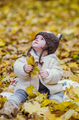 Toddler girl picking golden leaves in a park on a sunny day.