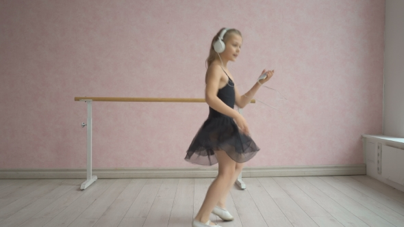 VideoHive Happy Little Girl In Headphones Listening To Music From Smartphone And Dancing 18689779