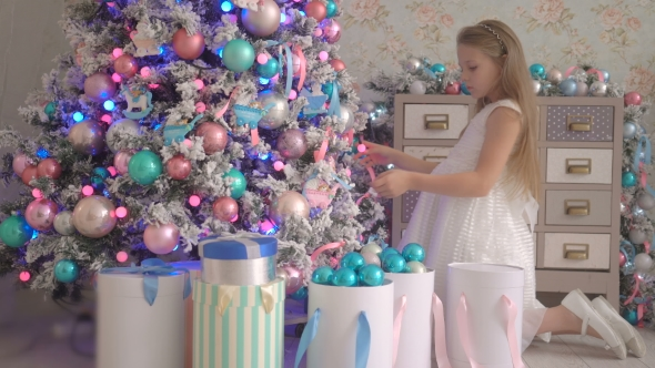 VideoHive Little Girl In White Dress With Gifts Near Decorated New Year Tree 18689943