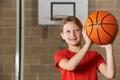 Girl Shooting Basketball In School Gym